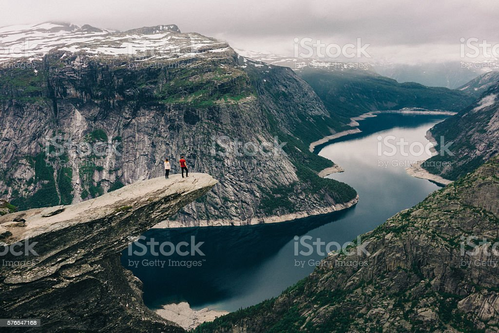Two people standing  on the Trolltunga stock photo