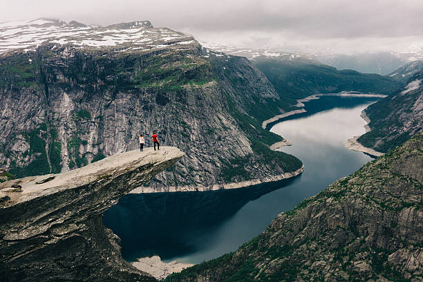 two people standing  on the trolltunga - noruega - fotografias e filmes do acervo