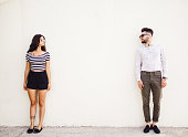 Two people standing on white wall background.