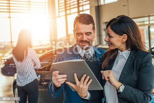 istock Two people talking about car contract in car salon. 883817810