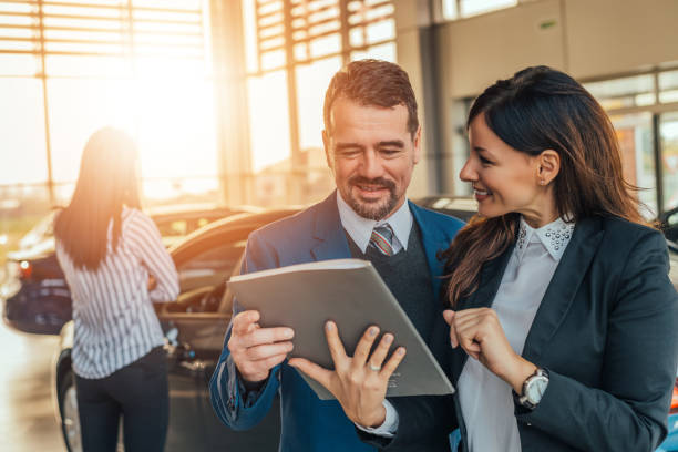 Two people talking about car contract in car salon. stock photo