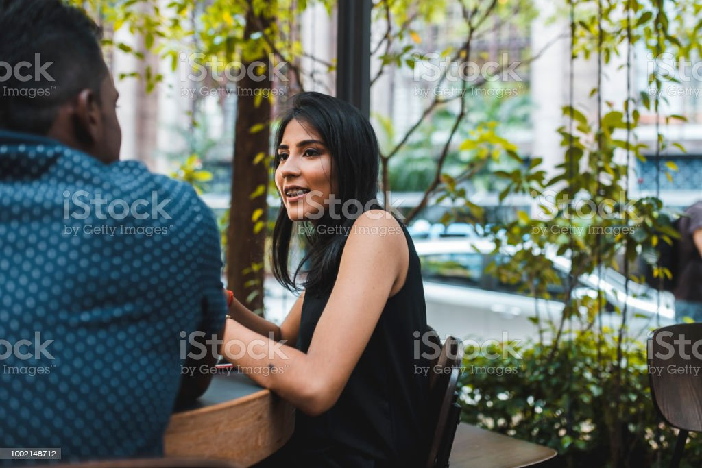 Two people talking outdoors at a cafe