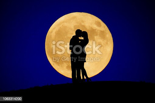 Two people to kiss the moon in back
