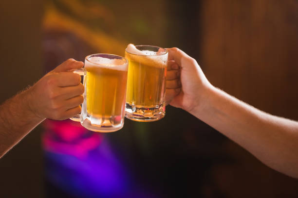 Two people toasting with mug beer Two people toasting with mugs full beer bohemia czech republic stock pictures, royalty-free photos & images