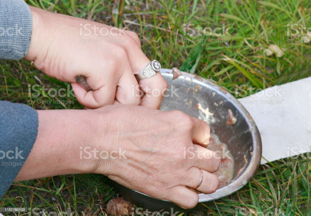Two people tourist eat stew from one cup on the nature, a metal...