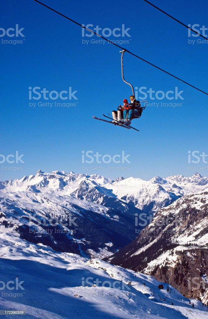 Two people using a ski lift to cross to the other side safe stock photo