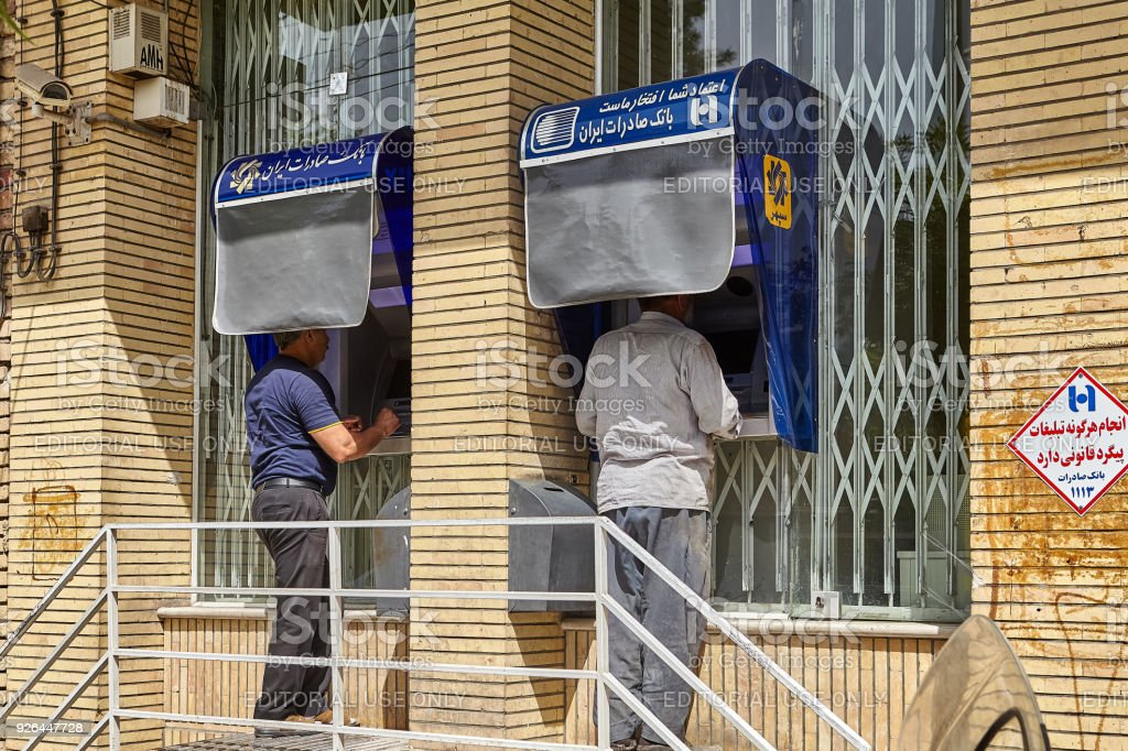 Two people using ATMs street outdoors, Kashan, Iran. stock photo
