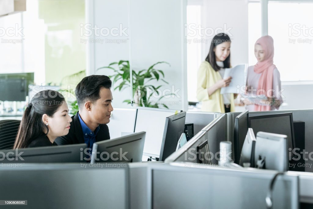 Businessman and woman using desktop computers, two women discussing...