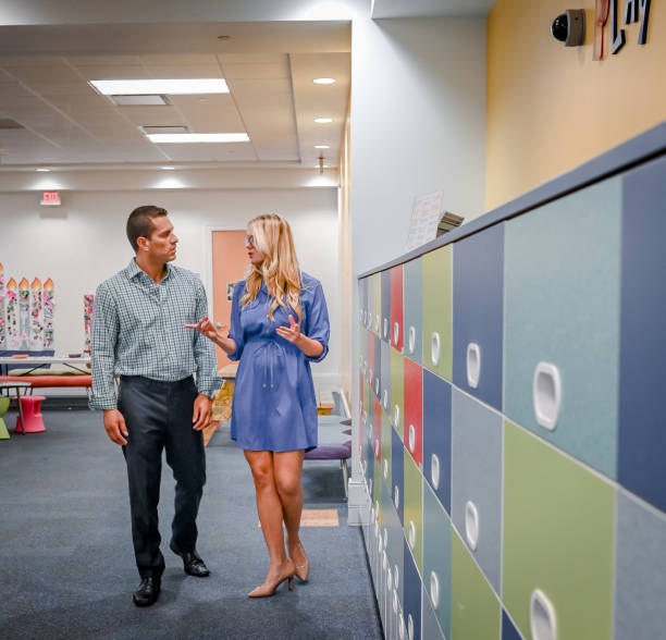 Two people walk around in a classroom, teachers or parent teacher conference stock photo