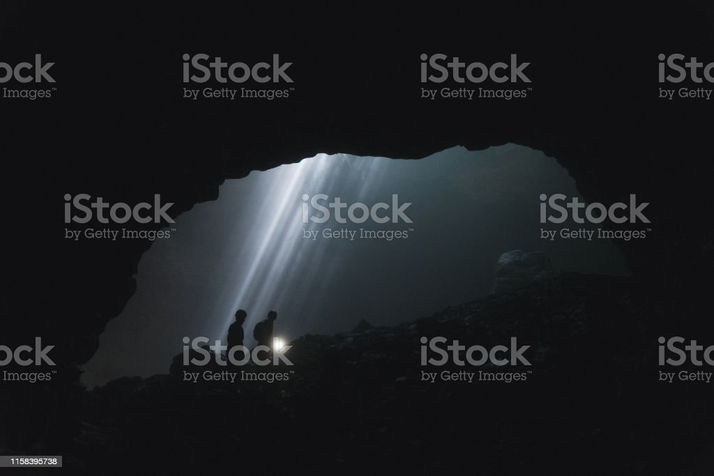 Silhouettes of two people walking in Jomblan Cave on the background...