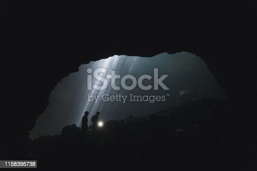Silhouettes of two people walking  in Jomblan Cave  on the background of sunbeams, Java, Indonesia