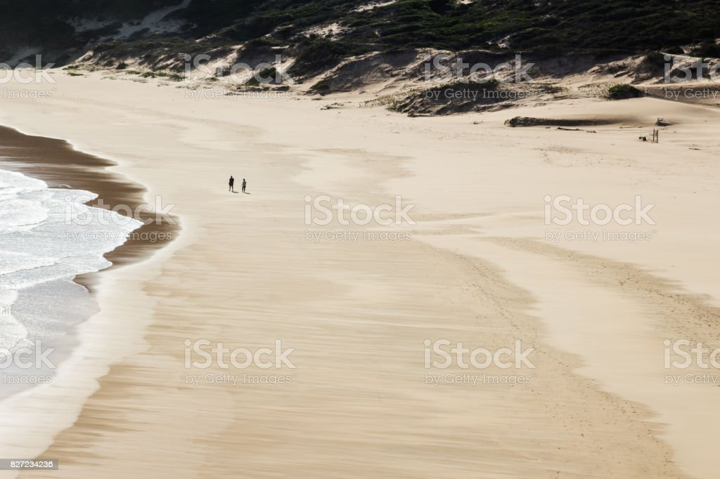 Two people walking on a quiet beach in Plettenberg bay, South Africa.. stock photo
