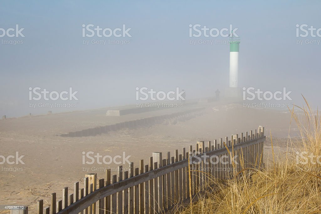 Two people walking on lighthouse pier on a misty morning stock photo