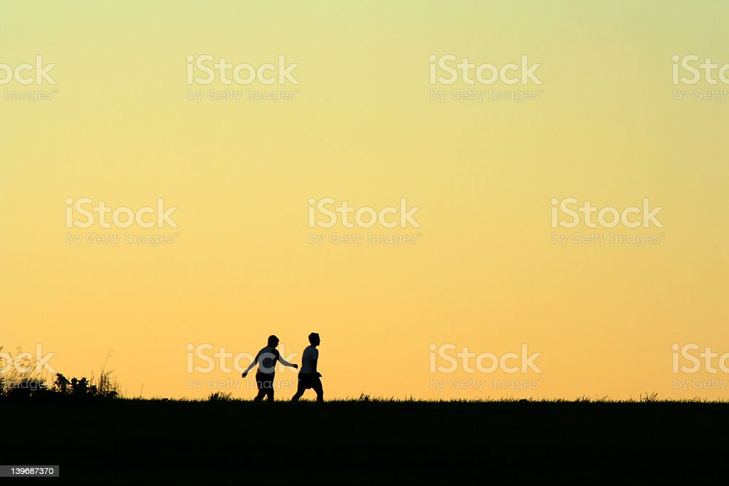 Two people walking outside at sunrise stock photo