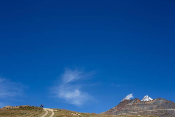 Zwei Personen gehen den Bergweg hinauf – Foto