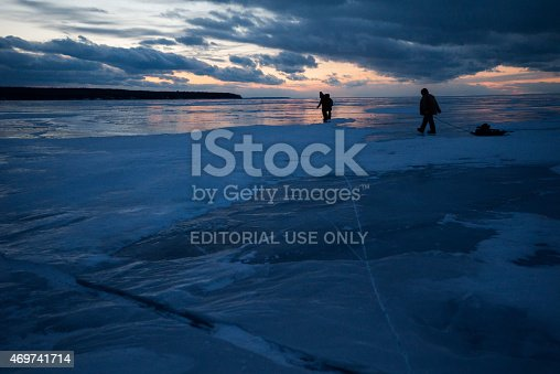 Wisconsin, USA - March 1, 2015: Two people walk across frozen Lake Superior at night after sunset returning from a visit to the famous ice caves at  Apostle Island National Lakeshore, Cornucopia, Bayfield County