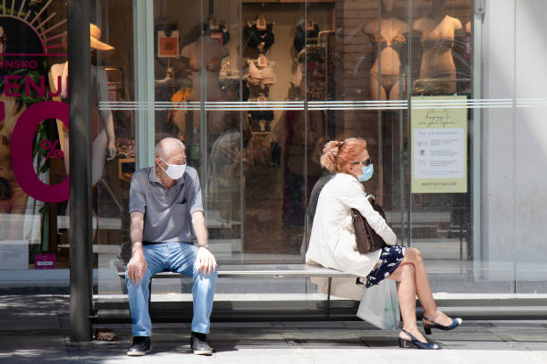 Two people wearing face surgical masks waiting for the public transport at bus stop
