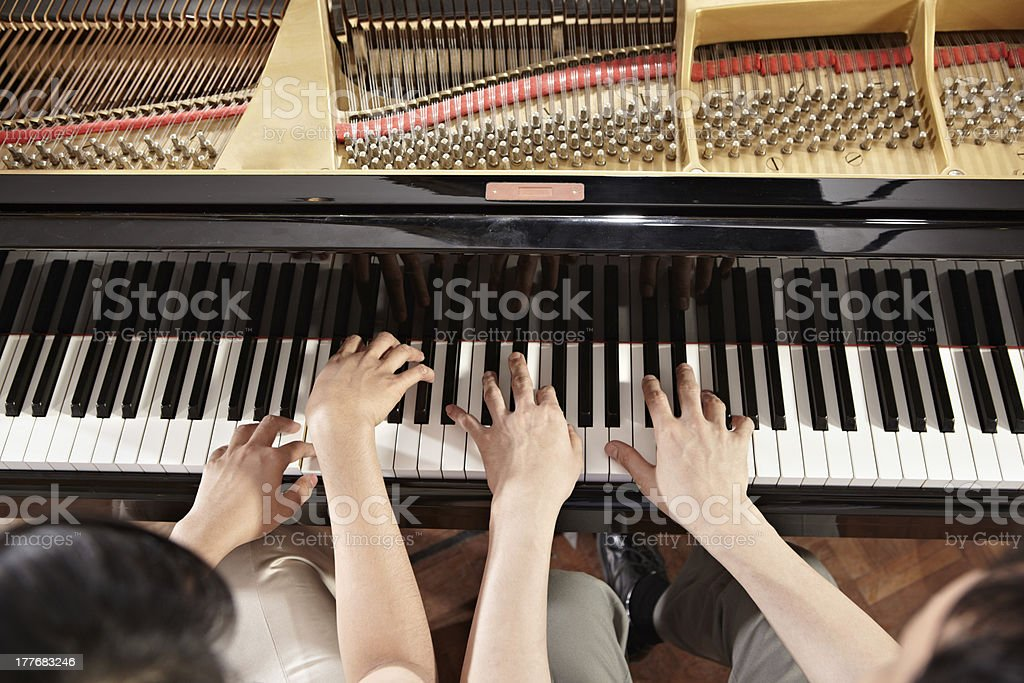 Two people wearing khaki pants playing the piano together stock photo