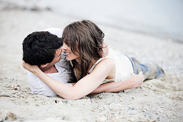 Two people who love each other laying in sand stock photo