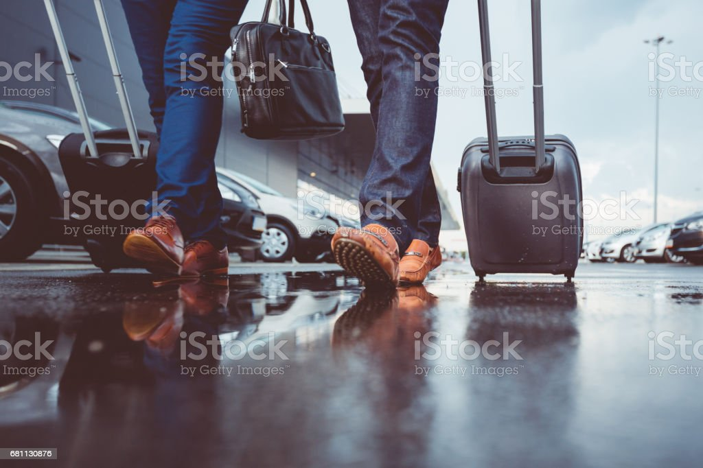 Two people with luggage walking at parking lot stock photo