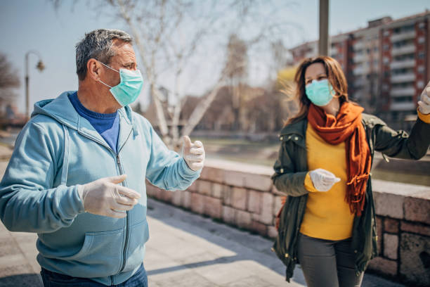 Two people with protective mask walking on the street in safe distance Man and woman, two people with protective mask walking and talking on the street in safe distance. avoidance stock pictures, royalty-free photos & images