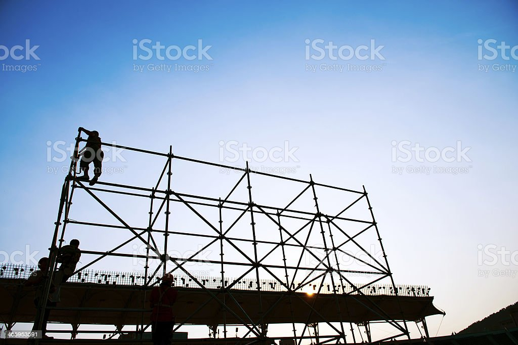 Two people working on a scaffolding at dusk stock photo