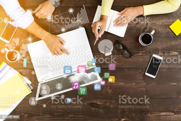 Two people working together on laptop at office with technological pattern