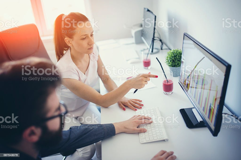 Two people working on computers stock photo
