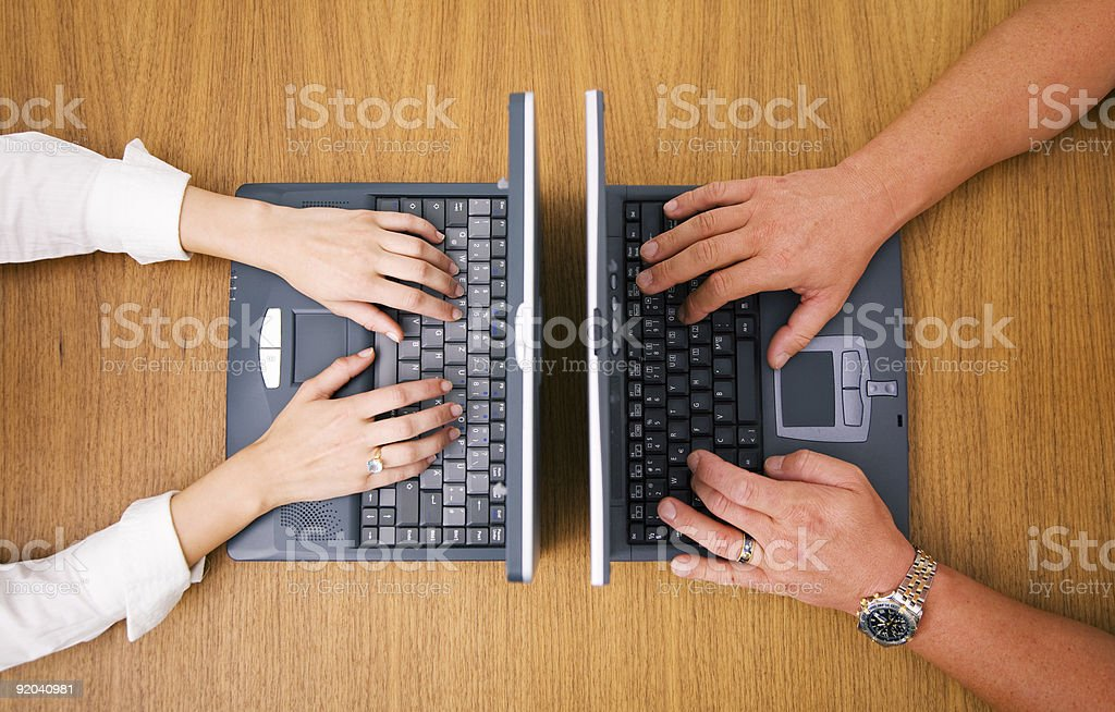 Two people working on laptops on opposite sides of table royalty-free stock photo