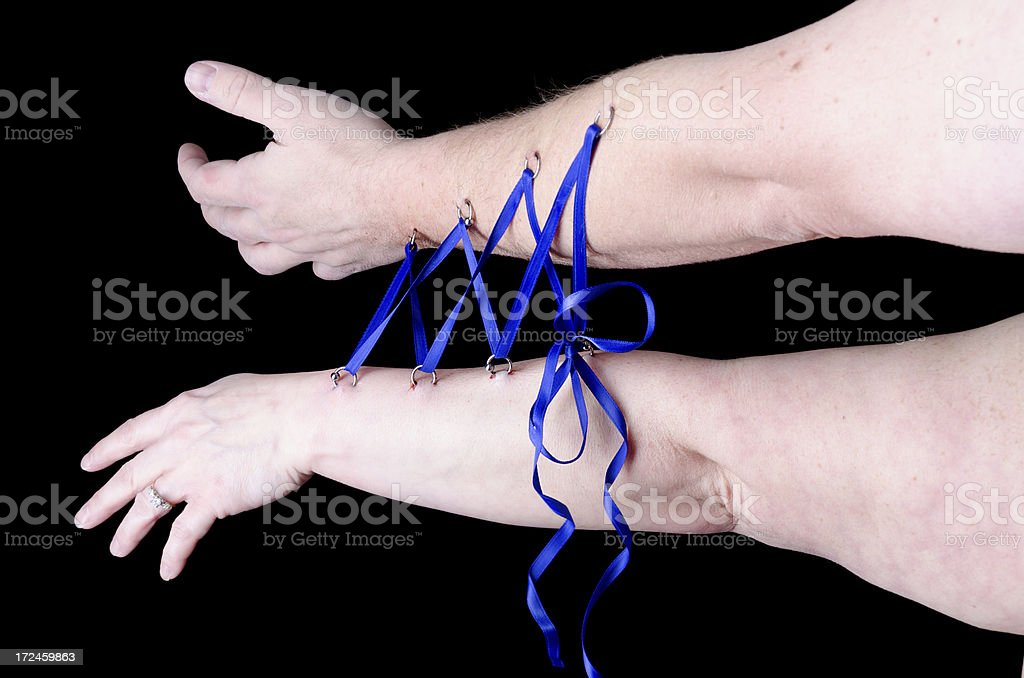Two peoples' arms laced together with ribbons royalty-free stock photo