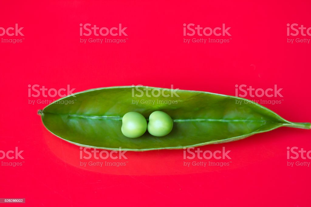 Two Perfect Peas in a Pod, Vibrant Red Background stock photo