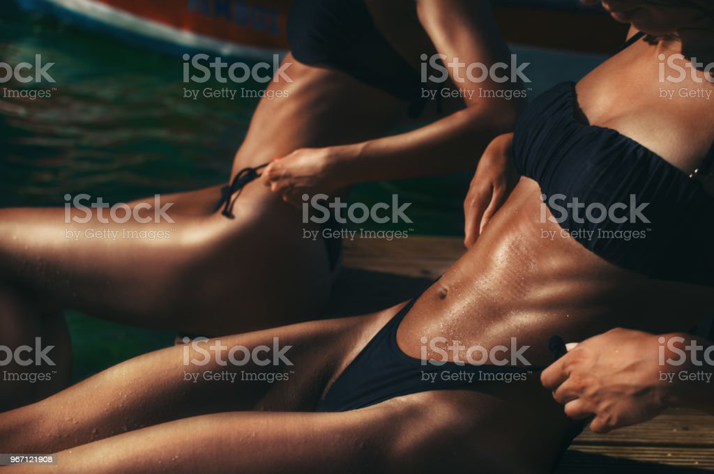 Two perfectly shaped young woman twins sunbathing by the sea showing their muscular tanned bodies stock photo