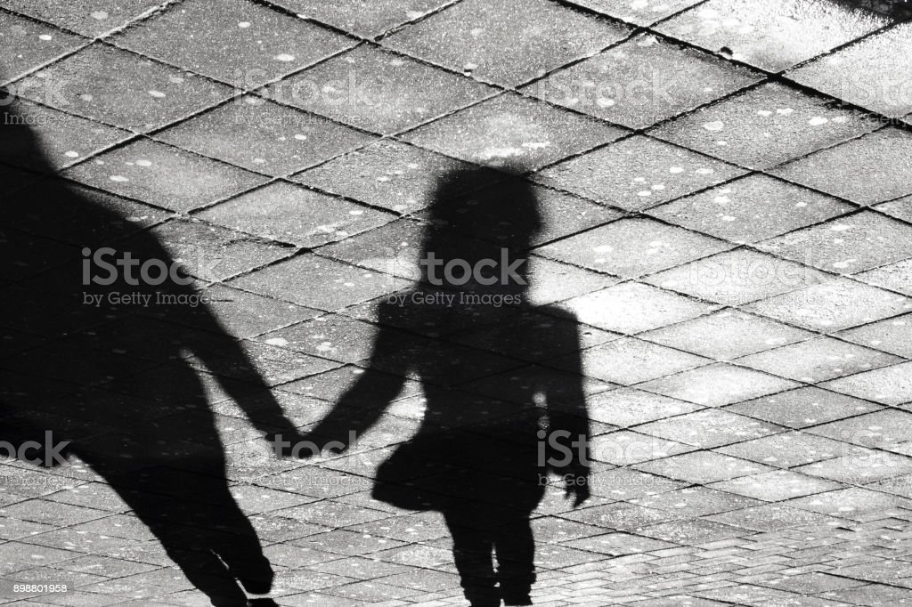 Two person holding hands shadow on a sidewalk stock photo