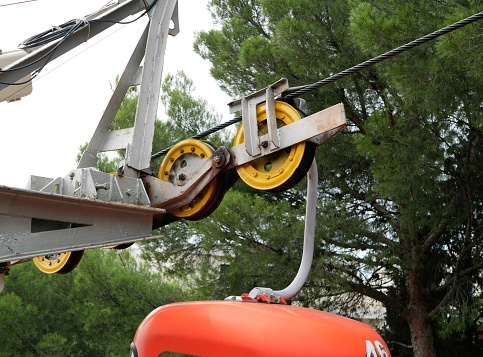 A two person lift cab is lifted on a cable against a background of green coniferous trees on a Sunny summer day