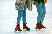 two persons in blue jeans are actively skating in red skates on an ice rink holding hands. Sport and hobbies. Holidays and winter fun