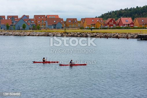Göteborg, Sweden - July 21 2019: Two persons kayaking by some houses..