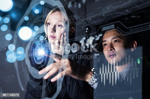 istock Two persons looking at graphical user interface. Futuristic business concept. 861148370