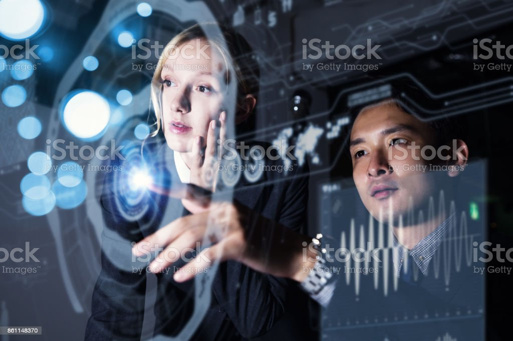 Two persons looking at graphical user interface. Futuristic business concept. stock photo