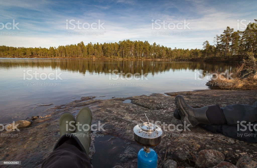 Two persons sitting at the edge of lake making coffe on a camp stove, pine forest in the wilderness of Norway stock photo