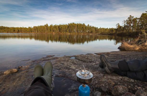 Dos personas sentadas en el borde del lago que hace café en un campamento de la estufa, bosque de pinos en el desierto de Noruega - foto de stock