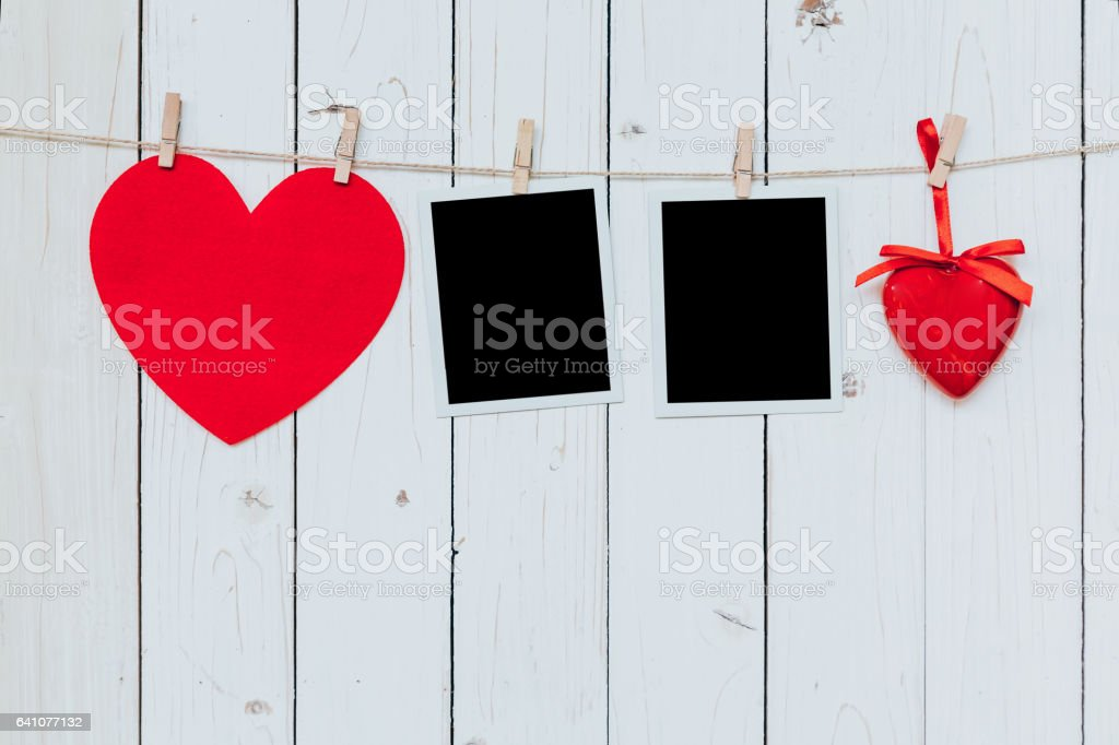 Two photo frame blank and red heart hanging on white wood background with space stock photo