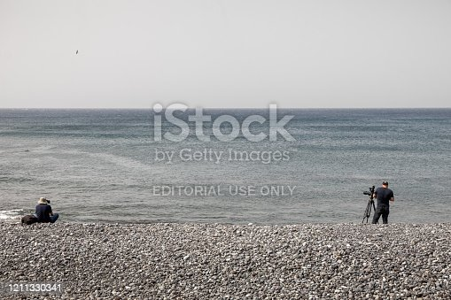 Los Christianos, Tenerife, Spain, February 4, 2020: Two photographers waiting for surfers and action by a calm sea on a stony beach