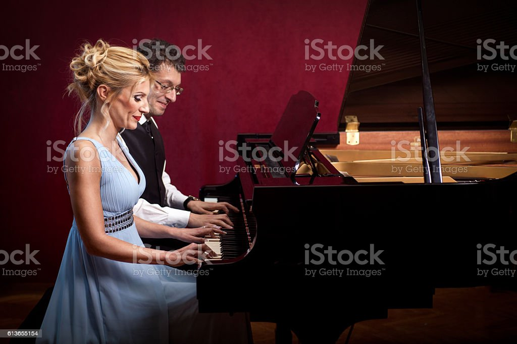 two beautiful young attractive woman and man playing piano