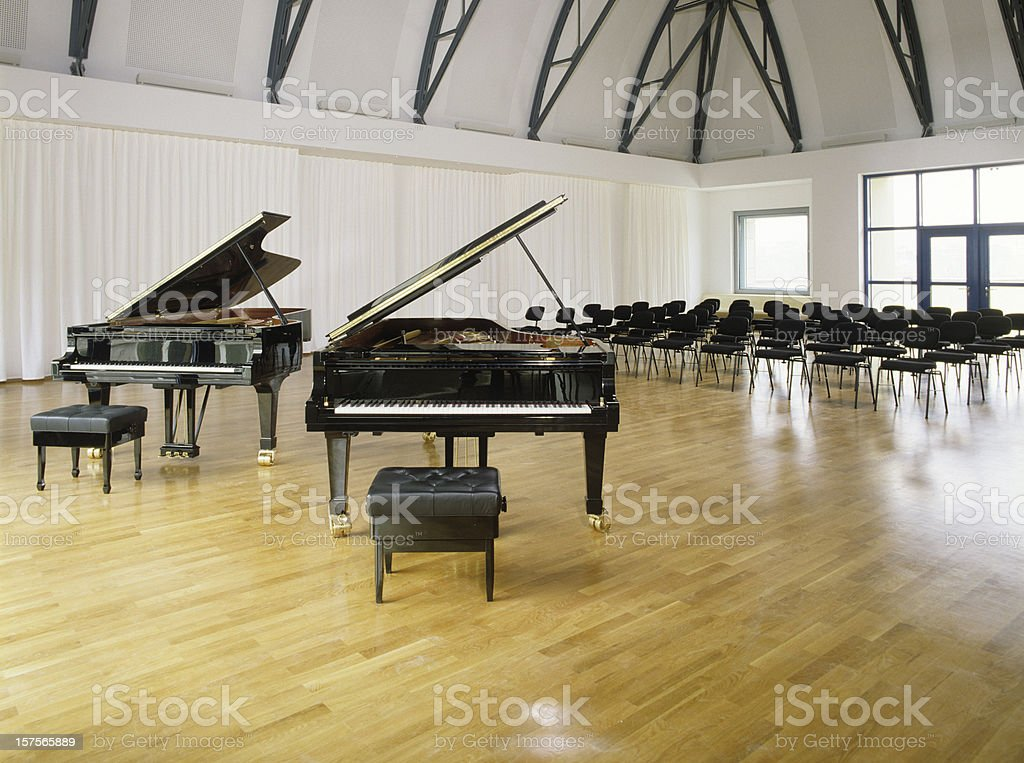 Two pianos in front of empty chairs royalty-free stock photo