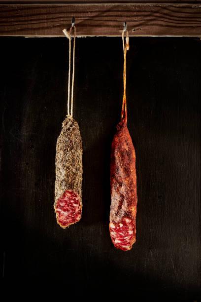 dos piezas de fuet colgando delante de una pared rústica. salchicha tradicional de cataluña, españa. - fuet sausages fotografías e imágenes de stock