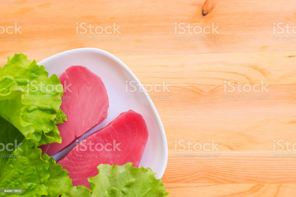 Two pieces of raw fresh tuna fillet on a plate with large leaves of a green salad on a wooden table. Delicious sea food easy. Greek cuisine stock photo