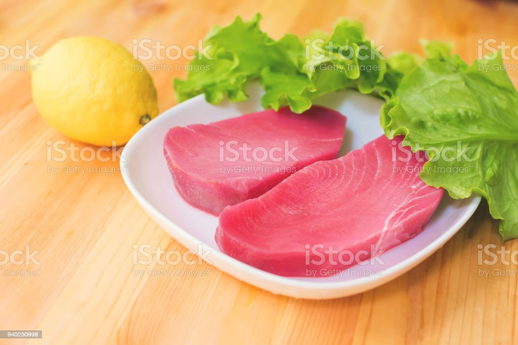 Two pieces of raw fresh tuna fillet on a plate with large leaves of green salad and yellow lemon on a wooden table. Delicious sea food easy. Greek cuisine stock photo