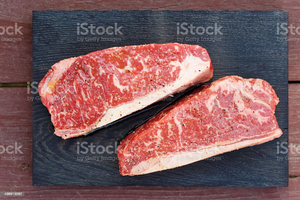Two pieces of raw striploin steak on wooden plank stock photo