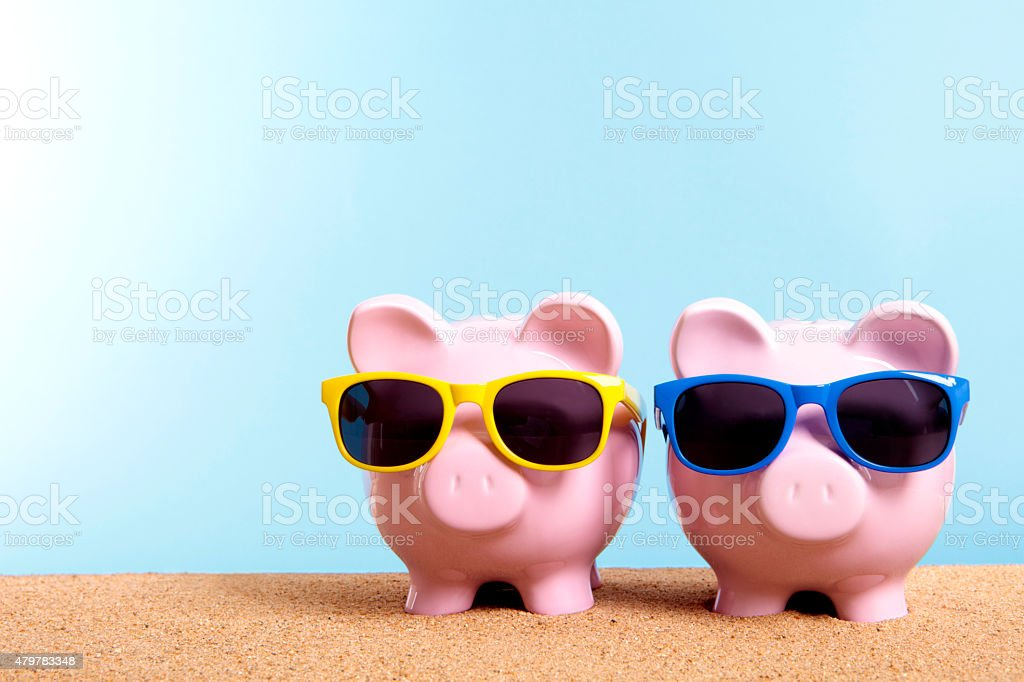 Two piggy banks on beach vacation stock photo