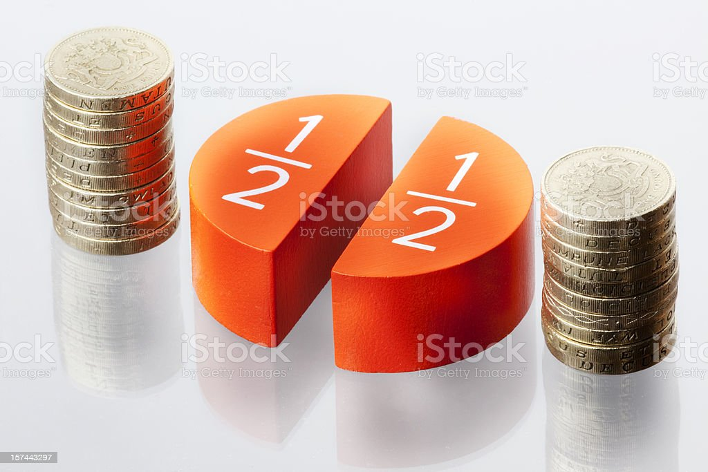 Two pile of coins and circle graphs denoting Fifty percent stock photo